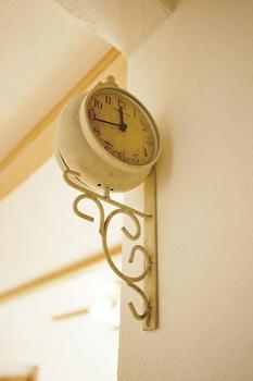 漆喰の壁と調和するアンティーク時計(シノスタイル・木もれ陽物語)